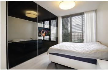 ארון הזזה שחור, עם דלתות זכוכוית שממוקם בחדר שינה