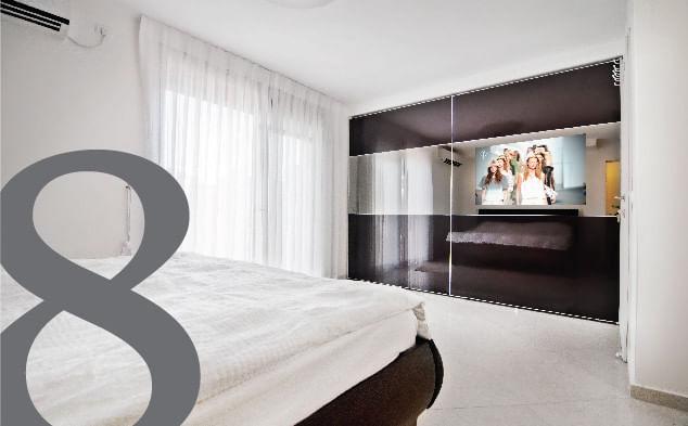 חדר שינה עם ארון הזזה של הרדור עם הסיפרה 8 בחזית התמונה